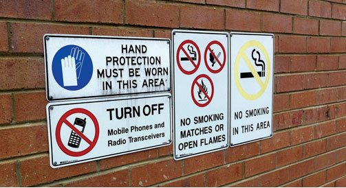 Engraving text on safety signs and symbols